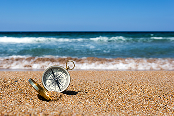 Gold compass on the beach sand ocean and blue sky representing directed trusts financial advisors