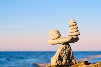 stones in balance blue sky and ocean on the background representing Trusts and Estate Planning